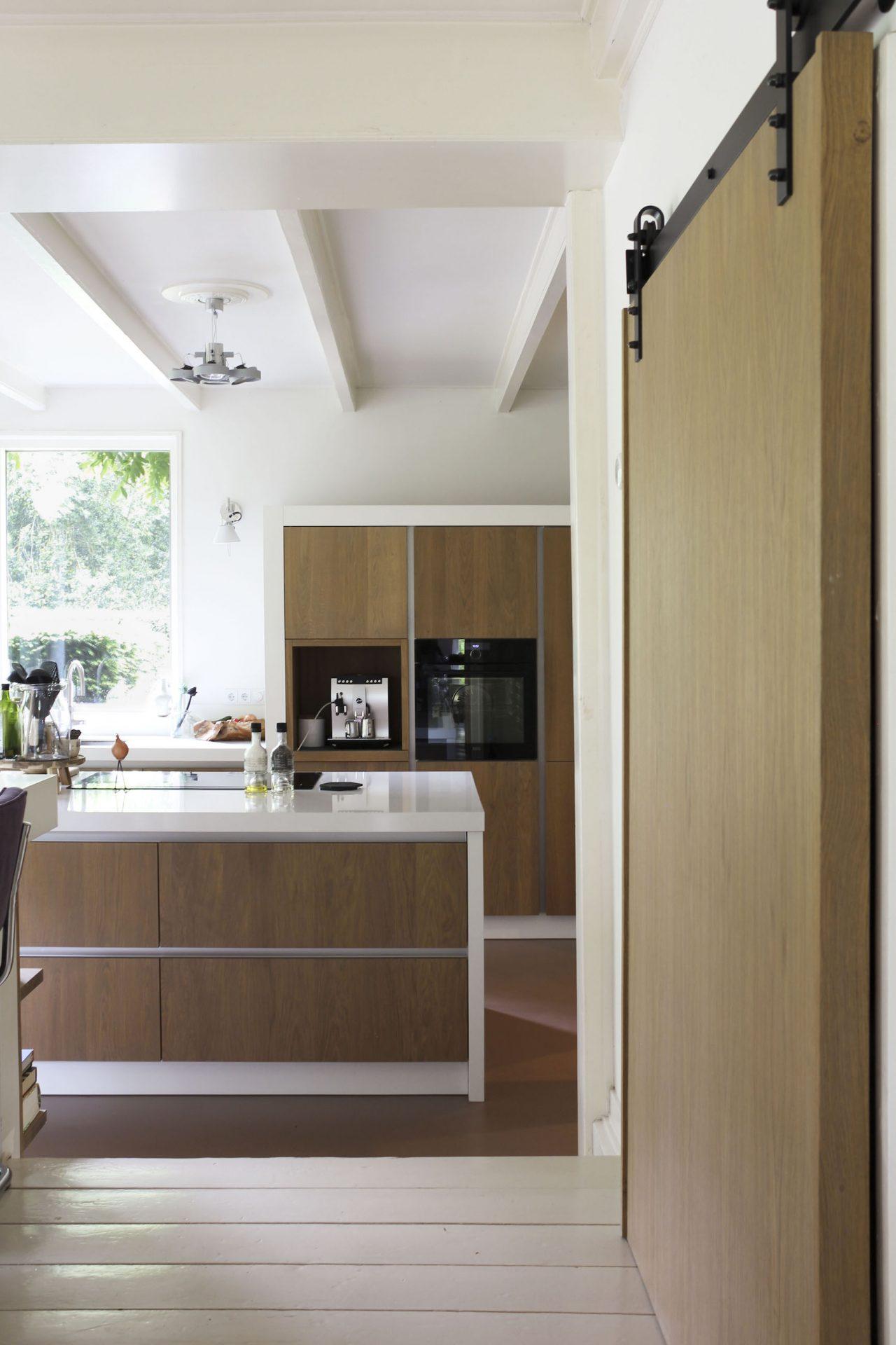 In het interieurontwerp speelt hout een grote rol dit zou je terug in de frontjes en de houten schuifdeur voor de servieskast.