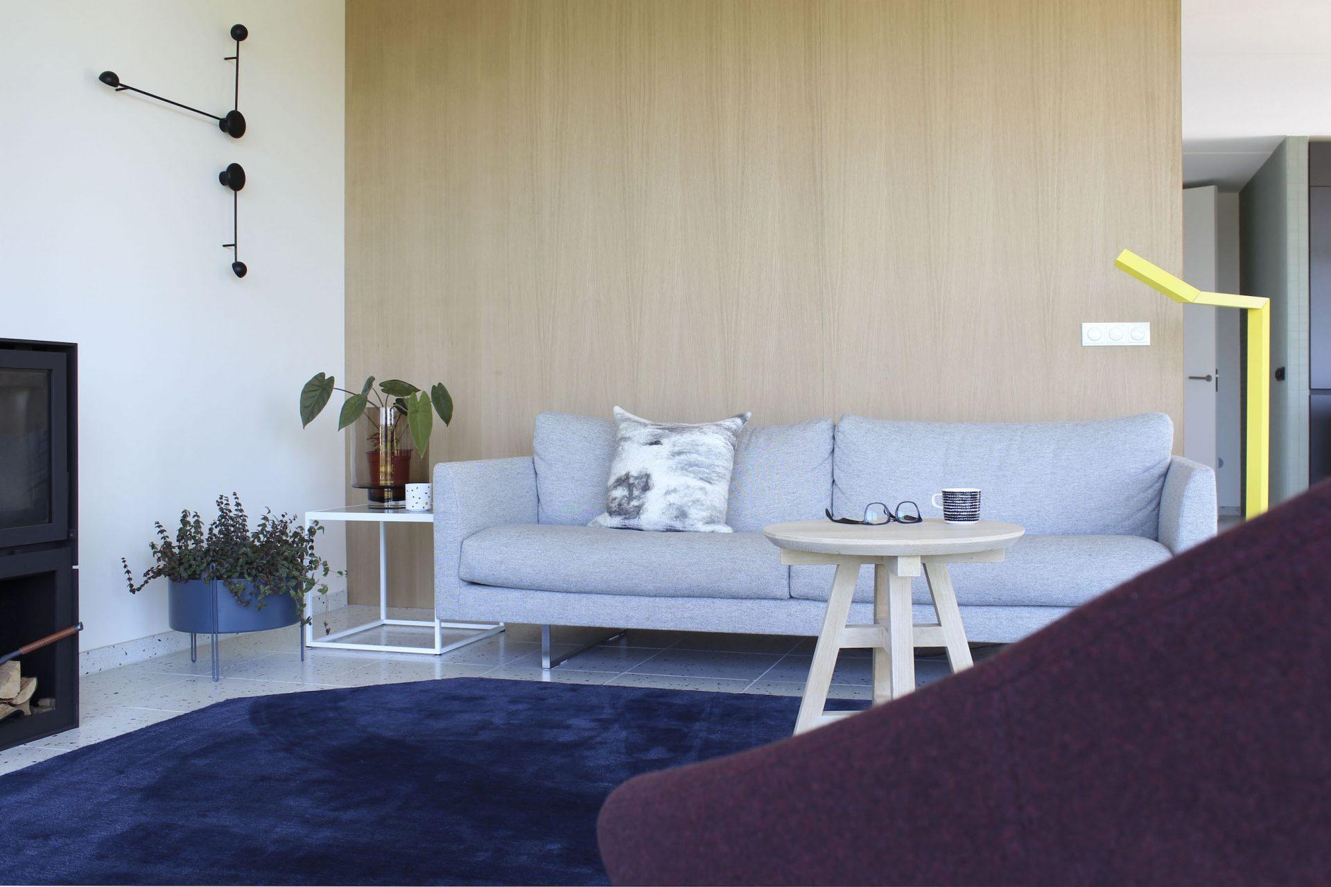 De zithoek is ingedeeld met wandverlichting, een wollen vloerkleed en stoffenbank. Maatwerk eikenhout wandbekleding is onderdeel van de binnenhuisarchitectuur.