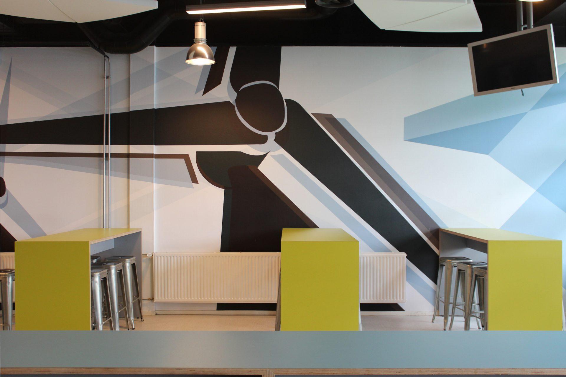 Grote diapositieve prints van windmolens ge��nspireerd op Andy Warhol op de muur van de centrale hal in ROC Friese Poort in deze projectinrichting.